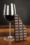 Glass of red wine and chocolate bar Stock Photos