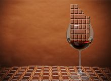 Glass with red wine and chocolate bar. Wine chocolate color red background view element Stock Photo