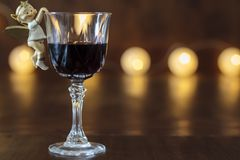 Glass of red wine with Christmas decoration. Glass of red wine with Christmas angel decoration royalty free stock images