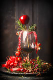 Glass of red wine with Christmas decorations and rosemary branches on table at dark wooden background Stock Image