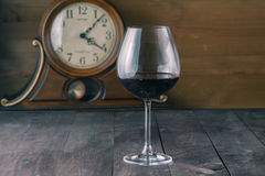 Glass of red wine with clock background Stock Image