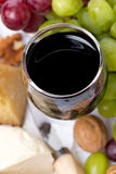 Glass of red wine close-up, cheese and grapes, top view Royalty Free Stock Photo