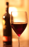 Glass of red wine. Close up image of a glass of red wine in a  restaurant setting with a bottle of red wine in the background Royalty Free Stock Photo