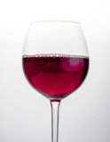 Glass of red wine close-up over white background.  Royalty Free Stock Photography