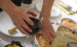 Glass of red wine close up in womans hand dining at a buffet. Royalty Free Stock Photo