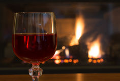 Glass of Red Wine. Closeup of a glass of wine with a fireplace in background Stock Photos