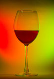 Glass with red wine on colours gradient background. Glass with red wine on gradient background of red yellow and green colours Royalty Free Stock Images