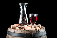 Glass of red wine and corks on old oak barrel Royalty Free Stock Photo
