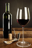 Glass of red wine, corkscrew and bottle on a table. Selective focus Royalty Free Stock Photo