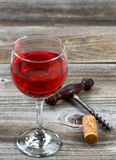 Glass of red wine with corkscrew and cork on aged wood Royalty Free Stock Photo