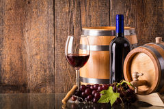 Glass of red wine with dark bottle and barrels Stock Image