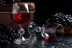 Glass of red wine on dark marble background. Cluster of blue gra Royalty Free Stock Image