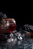 Glass of red wine on dark marble background. Cluster of blue gra Stock Photography