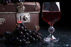 Glass of red wine on dark marble background. Cluster of blue gra Stock Images