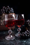 Glass of red wine on dark marble background. Cluster of blue gra Stock Photos