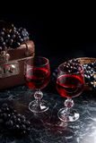 Glass of red wine on dark marble background. Cluster of blue gra Royalty Free Stock Photo
