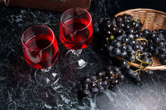 Glass of red wine on dark marble background. Cluster of blue gra Royalty Free Stock Images