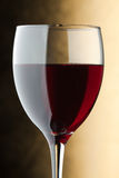 A glass of red wine. Detail. Fragment of a glass of red wine on a golden background royalty free stock image