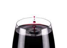 Glass of red wine, drops in motion, studio shot Stock Photography