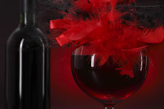 Glass of red wine with a feather hat. On the backgroung of the bottle Royalty Free Stock Image