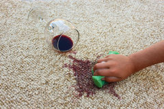 Glass of red wine fell on carpet. Female hand cleans the carpet Royalty Free Stock Photo