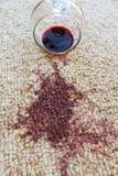 Glass of red wine fell on carpet. Wine spilled on carpet Stock Photo
