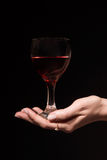 Glass with a red wine in a female hand Royalty Free Stock Image