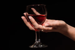 Glass with a red wine in a female hand Stock Photo