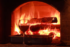 Glass of red wine at firewood oven background Royalty Free Stock Photos