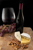 Glass of red wine with food. On wooden table Royalty Free Stock Images