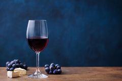 Glass of red wine with fresh grape and cheese on wooden table. Blue background. Copy space. Glass of red wine with fresh grape and cheese on wooden table. Blue stock image