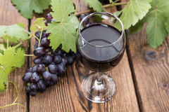 Glass with Red Wine. And fresh Grapes on wooden background Royalty Free Stock Photography