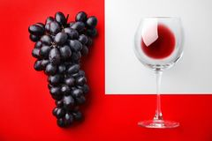 Glass with red wine and fresh ripe juicy grapes. On color background, top view royalty free stock photography
