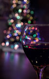 Glass of Red Wine in Front of Christmas Tree Royalty Free Stock Photography