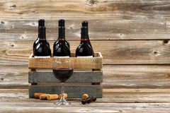 Glass of red wine and full bottles in wood crate on rustic woode Royalty Free Stock Photos