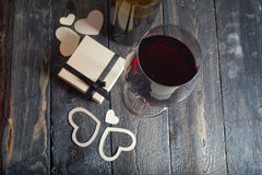 Glass of red wine and a gift on a wooden background Royalty Free Stock Photo