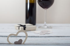 Glass of red wine and a gift on a wooden background Stock Images