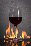 Glass. Red wine glass  with fire splash in front of stone granit Royalty Free Stock Photography