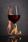 Glass. Red wine glass  with fire splash in front of stone granit Royalty Free Stock Photos