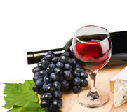 Glass of red wine with grapes Royalty Free Stock Photos