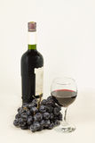A glass of red wine and grapes. A glass of red wine, bottle and grapes on a light background royalty free stock image