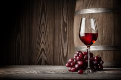 Glass of red wine with grapes and barrel. On the background of wooden wall Royalty Free Stock Image