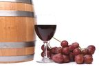 A glass of red wine with grapes and barrel. Royalty Free Stock Photography