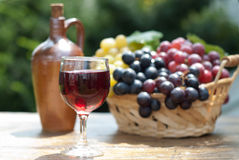Glass of red wine and grapes in a basket Stock Photography