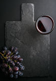 Glass of red wine and grapes on black slate stone board over dark background. Top view, copy space stock photos