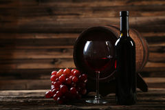 Glass of red wine with grapes on the brown wooden background Royalty Free Stock Photography