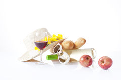 Glass of red wine,grapes and cheese isolated on white. Picnic setting with wine, fruits and summer hat isolated on white Stock Image