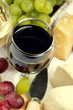 Glass of red wine, grapes and cheese, top view, close-up Stock Images