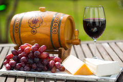 Glass of red wine , grapes and cheese on a tray in the garden. For picknick, small wine barrel Royalty Free Stock Images