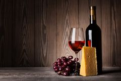 Glass of red wine with grapes and cheese Royalty Free Stock Images
